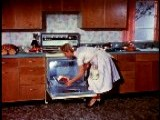 1958 Housewife In Kitchen Putting Roast Into Oven + Closing Oven