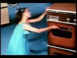 1960s High Angle Woman In Dress Dancing + Opening Oven In Studio
