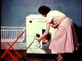 1955 Housewife Kneeling And Unloading Clothes From Dryer Into Basket
