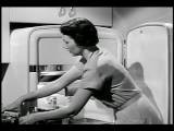 B W 1950s Zoom Out Housewife Loading Up Freezer + Refrigerator With Groceries