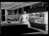 B W 1950s Woman Taking Food From Refrigerator In Futuristic Kitchen + Putting It