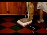 Medium Shot Legs Of Woman As She Vacuums Linoleum Floor In Kitchen