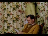 Medium Shot Housewife Bringing Cocktail To Man Reading Magazine, Then Sitting An
